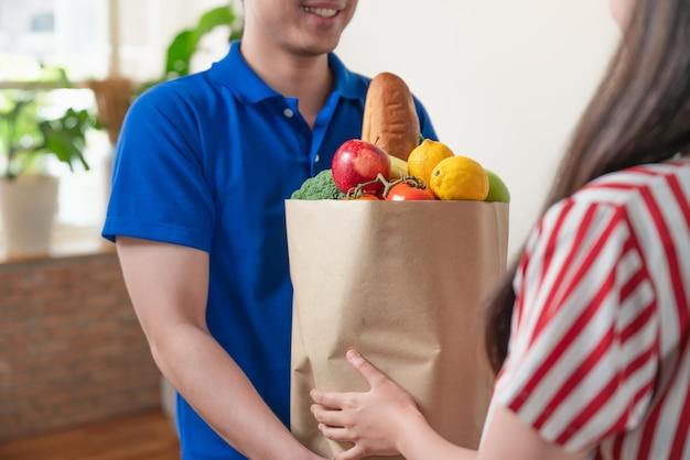 Asiatischer junger lieferbote in der blauen hemduniform, die zu hause der frau neues lebensmittel der pakettasche liefert lebensmittelladen-zustelldienst.