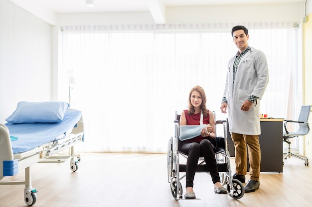 Asiatischer junger mann arzt der überprüfung der schiene den arm der weiblichen patientenhand aufgrund mit gebrochenem arm für eine bessere heilung mit einem lächeln im rollstuhl sitzen im zimmer krankenhaus