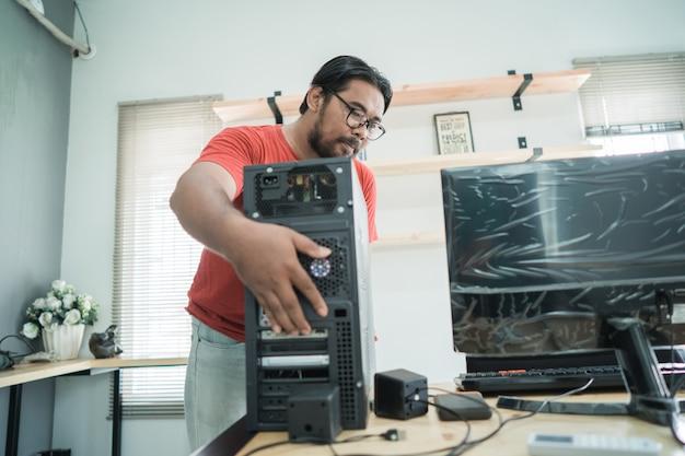 Asiatischer junger mann behebt ein problem mit dem server des personalcomputers