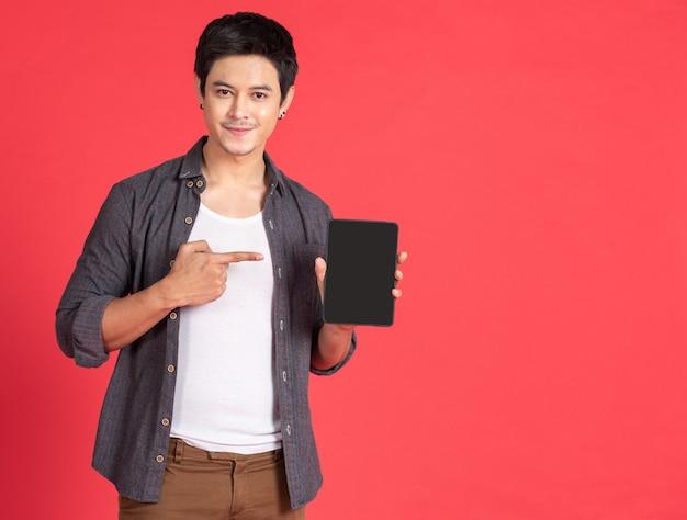 Asiatischer junger mann benutzt telefon tablette