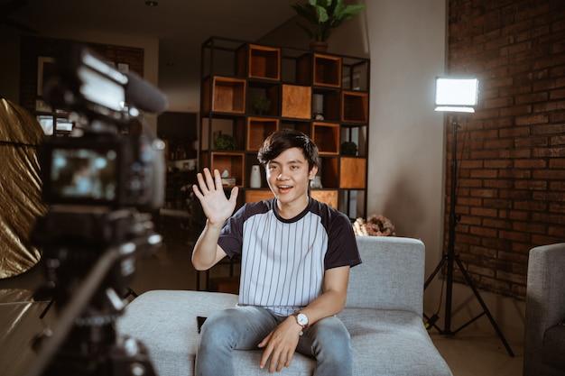 Asiatischer junger mann-blogger, der vlog aufzeichnet, das mit kamera spricht