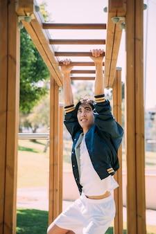 Asiatischer junger mann, der am klettergerüst ausarbeitet