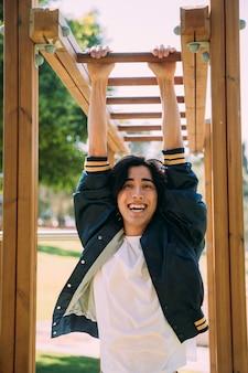 Asiatischer junger mann, der an den kletterstangen hängt