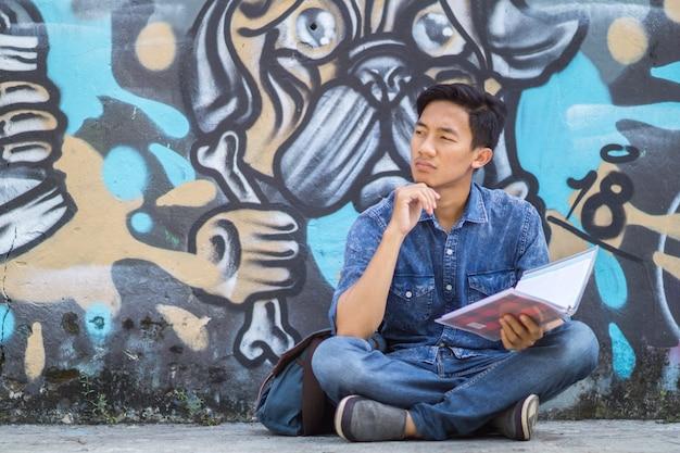 Asiatischer junger mann, der an ideen im park unter verwendung des buches denkt
