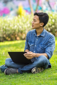Asiatischer junger mann, der an ideen im park unter verwendung des laptops denkt