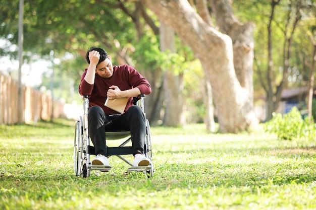 Asiatischer junger mann, der auf dem rollstuhl im parkkrankenhaus sitzt