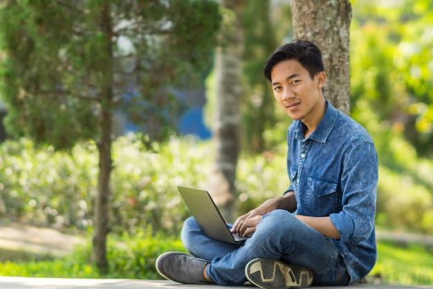 Asiatischer junger mann, der computer im freien verwendet
