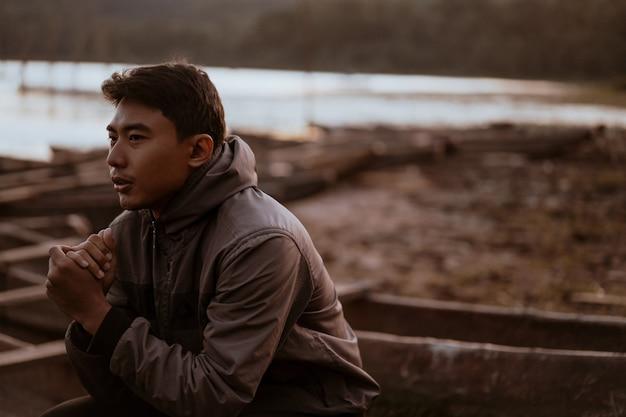 Asiatischer junger mann, der den kalten morgen genießt