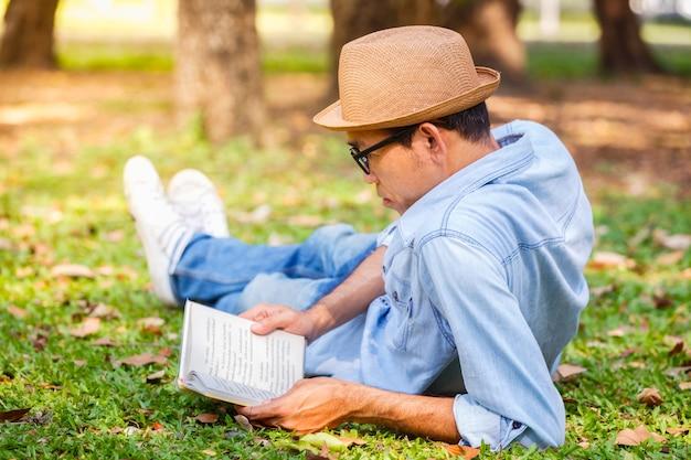 Asiatischer junger mann, der ein buch auf dem gras im park liest