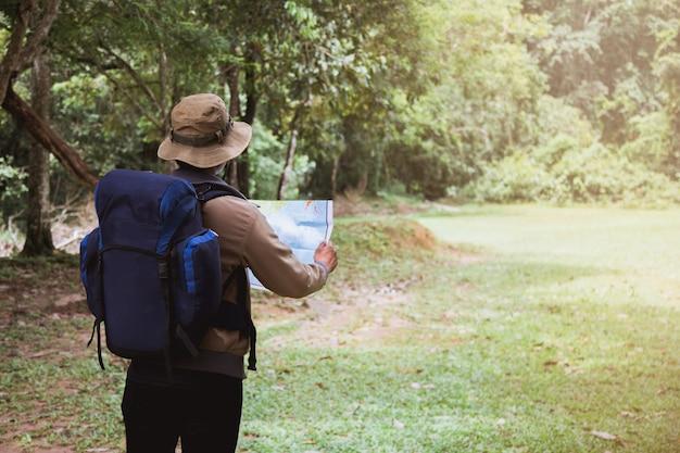 Asiatischer junger mann, der einen rucksack trägt und einen hut trägt