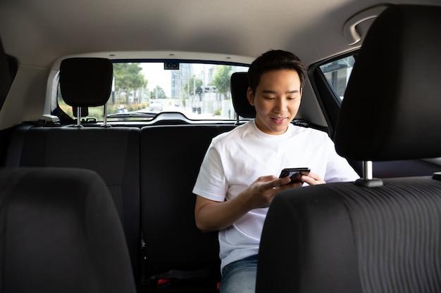 Asiatischer junger mann, der einen smartphone im rücksitz des autos verwendet