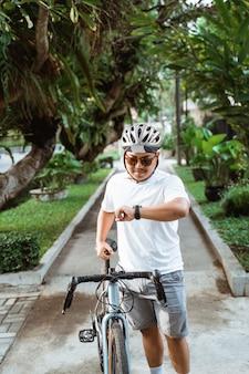 Asiatischer junger mann, der helmspaziergang mit rennrad trägt, wenn sie ihre uhr schaut