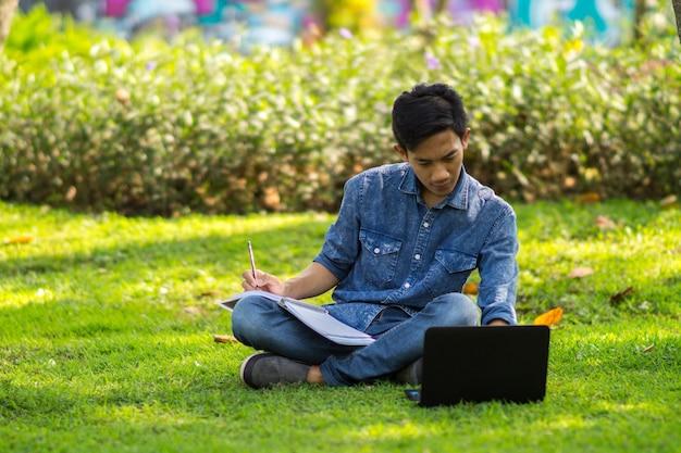 Asiatischer junger mann, der ideen auf seinem laptop sucht und in sein buch schreibt