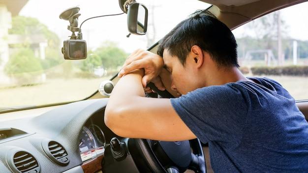 Asiatischer junger mann, der in seinem auto schläft.