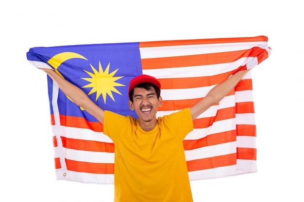 Asiatischer junger mann, der malaysia flagge hält