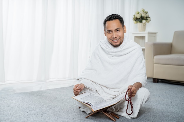 Asiatischer junger mann, der mit al-qur'an und gebetsperlen betet