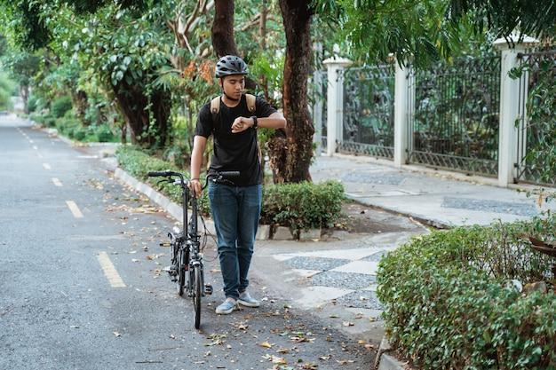 Asiatischer junger mann, der mit faltrad geht, während sie ihre uhr schaut