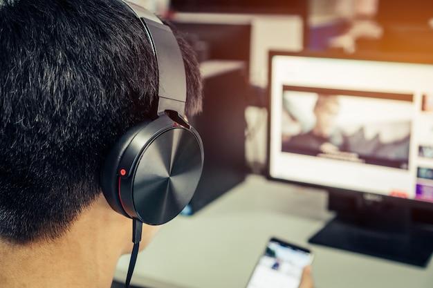 Asiatischer junger mann, der mit kopfhörern und laptop hört