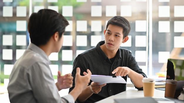 Asiatischer junger mann, der mit papierdokument auf modernem büro sich berät.