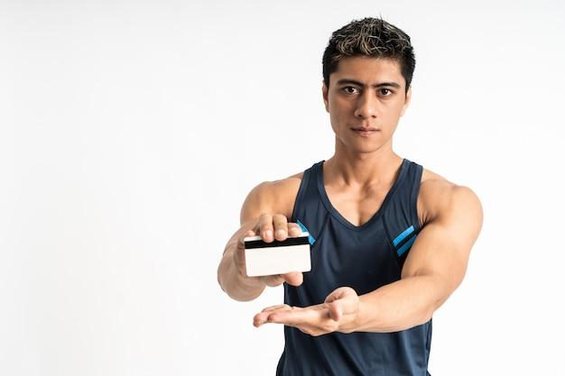 Asiatischer junger mann, der sportbekleidungsstand trägt, der vorwärts geschenkkarte mit zwei händen gegenübersteht