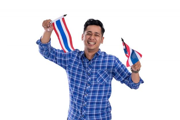 Asiatischer junger mann, der thailand-flagge hält