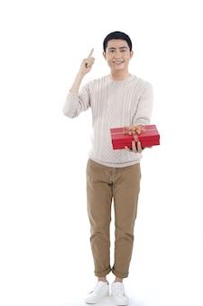 Asiatischer junger mann, der weihnachtsgeschenkbox mit rotem band gibt