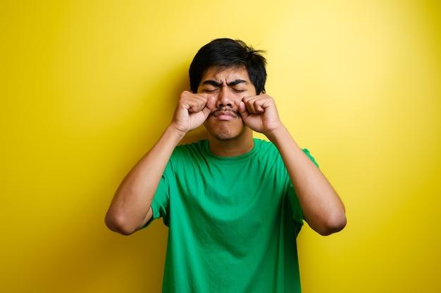 Asiatischer junger mann in grünem t-shirt weint seine augen, traurige depression frustration hoffnungsloser ausdruck vor gelbem hintergrund
