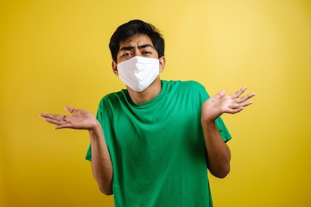 Asiatischer junger mann mit chirurgischer maske zuckt mit den schultern, ich weiß nicht, geste, gegen gelbe geste