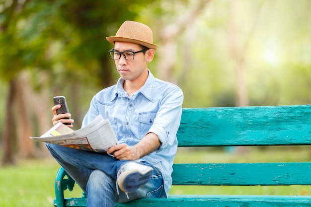 Asiatischer junger mann mit dem hut, der auf einer holzbank sitzt und eine zeitung liest und mitteilung überprüft