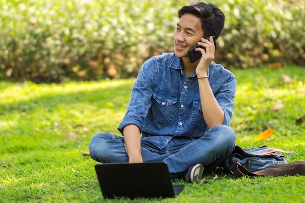 Asiatischer junger mann mit einem laptop und einem smartphone, die draußen in einem park sitzen