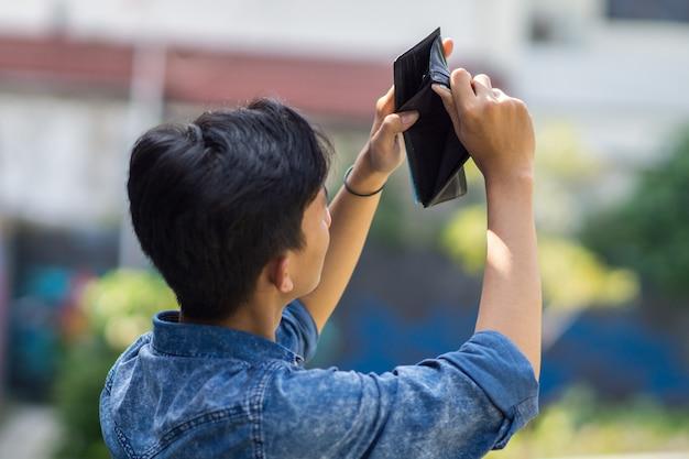 Asiatischer junger mann nahm eine leere brieftasche, asiatischer junger mann hat kein geld