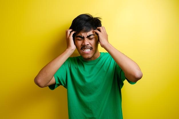 Asiatischer junger mann sieht verärgert aus und drückt sich vor kopfschmerzen den kopf mit den händen zusammen. das konzept von stress und migräne.