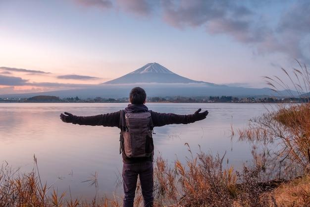 Asiatischer junger mann steht am morgen auf dem berg fuji auf dem kawaguchiko-see