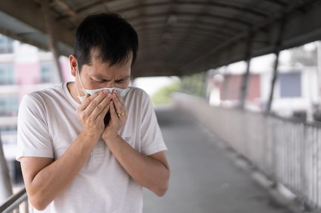 Asiatischer junger mann trägt eine maske und hustet von luftverschmutzung von pm 2.5