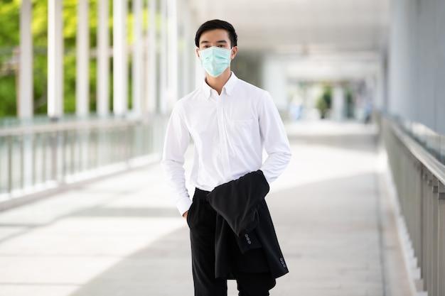Asiatischer junger mann tragen medizinische gesichtsmaske zum schutz coronavirus und pm2.5 in thailand