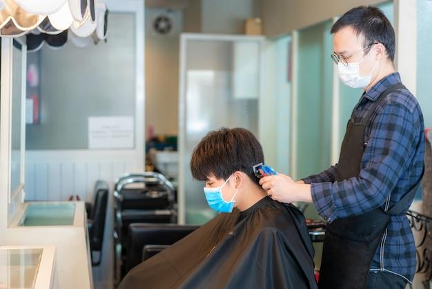 Asiatischer junger mann und friseur tragen medizinische maske, um sich während des romans coronavirus, covid-19 im barbershop hair care service zu schützen.