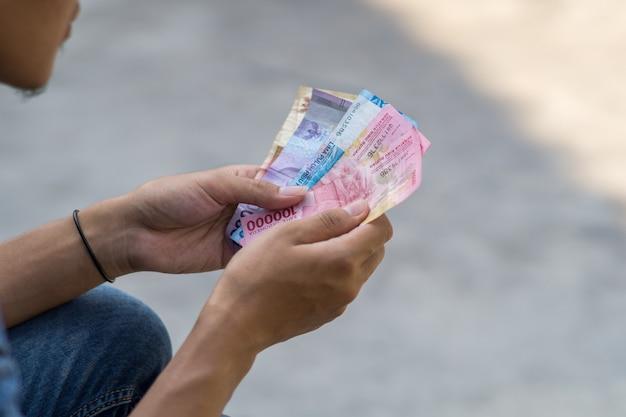 Asiatischer junger mann zählt geld