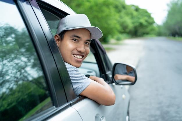 Asiatischer junger mannfahrer schaut von den offenen fenstern zurück