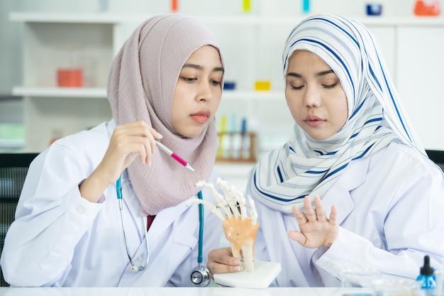 Asiatischer junger muslimischer wissenschaftsstudent, der das experiment im labor an ihrer universität macht. muslimische wissenschaftler untersuchen eine chemische probe. biotechnologieentwicklung im asiatischen länderkonzept.