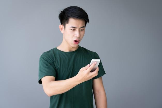 Asiatischer junger schöner mann, der smartphone verwendet