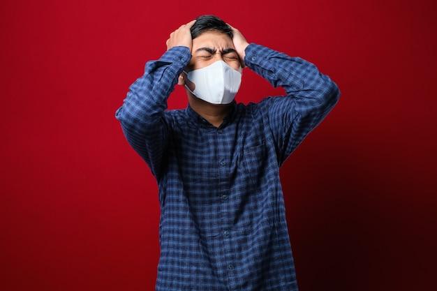 Asiatischer junger student, der flanellhemd trägt, verspürt schmerzen auf dem kopf und trägt eine schutzmaske, um die ausbreitung des corona-virus vor rotem hintergrund zu verhindern