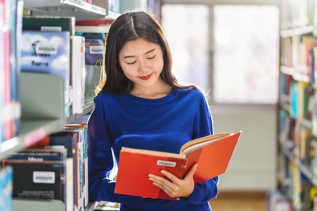 Asiatischer junger student im freizeitanzug, der das buch im bücherregal in der bibliothek steht und liest