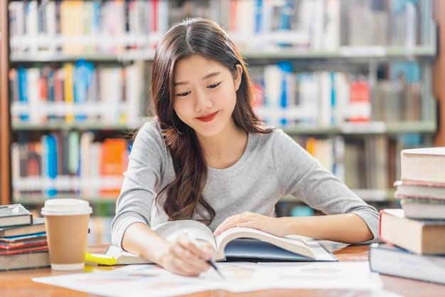 Asiatischer junger student im freizeitanzug, der in der bibliothek der universität oder des colleges liest und hausaufgaben macht