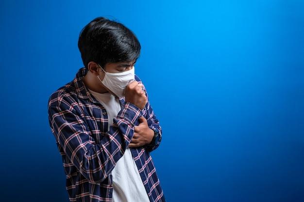 Asiatischer junger student leidet an husten mit gesichtsmaskenschutz vor blauem hintergrund