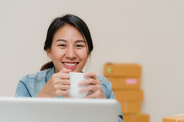 Asiatischer junger unternehmergeschäftsfrauinhaber von kmu, das produkt auf lager online prüfen, sparen zum computer und zu trinkendem kaffee, die zu hause arbeiten.