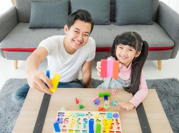 Asiatischer junger vater und tochter sitzen drinnen auf dem boden und spielen mit spielzeug und lächeln