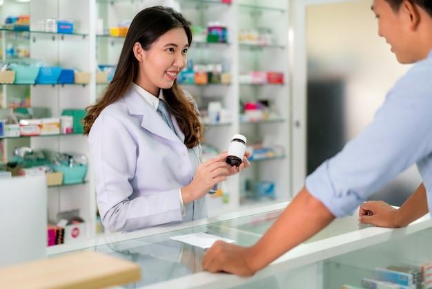 Asiatischer junger weiblicher apotheker mit einem reizenden freundlichen lächeln und der erklärung von medizin ihrem kunden in der apothekendrogerie.
