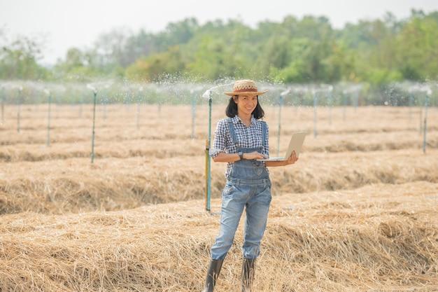 Asiatischer junger weiblicher landwirt im hut, der im feld steht und auf tastatur des laptop-computers tippt. frau mit laptop überwacht arbeit auf ackerland, konzeptökologie, transport, saubere luft, lebensmittel, bioprodukt Premium Fotos