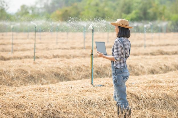 Asiatischer junger weiblicher landwirt im hut, der im feld steht und auf tastatur des laptop-computers tippt. frau mit laptop überwacht arbeit auf ackerland, konzeptökologie, transport, saubere luft, lebensmittel, bioprodukt