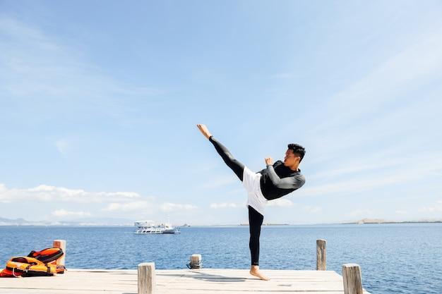 Asiatischer kämpfer mit taekwondo-kick posiert mit meer im hintergrund